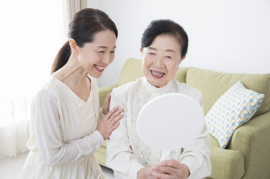 訪問カット後、鏡を見て嬉しそうに微笑む高齢女性と娘