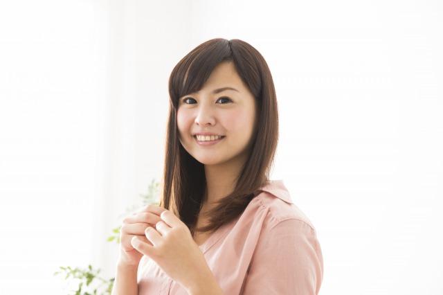 髪をいじりながら微笑んでいる女性