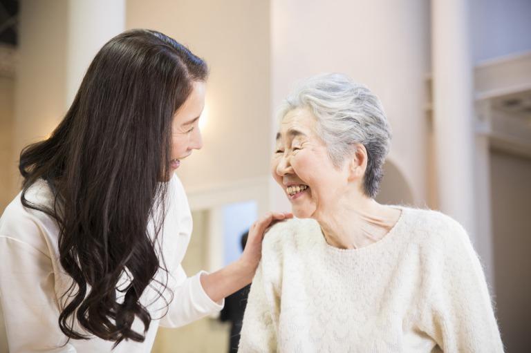 微笑む高齢のお客様と、訪問美容師