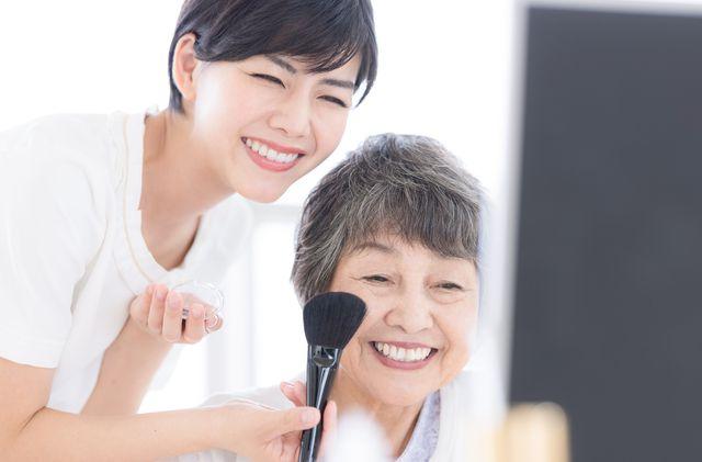 鏡を見て微笑むマダムと訪問美容師