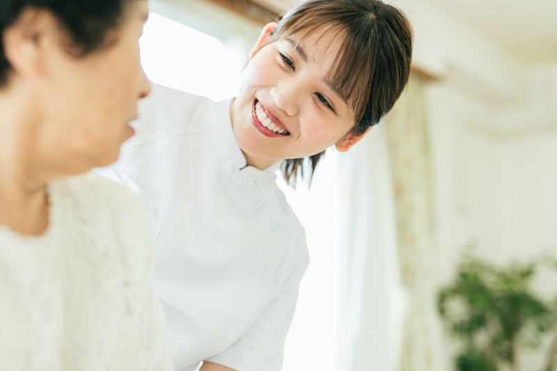 高齢者に笑顔で接する女性