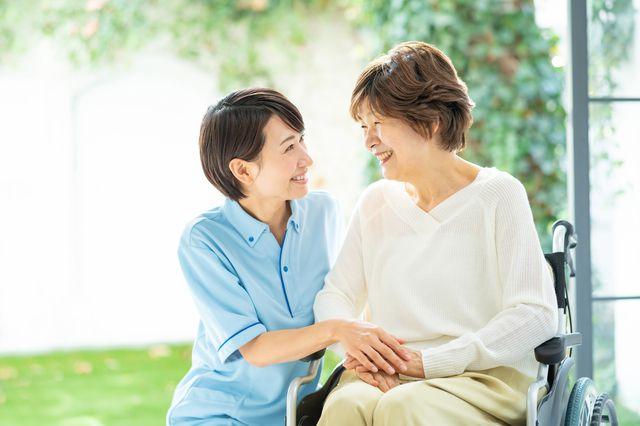 高齢者と笑顔で話す女性